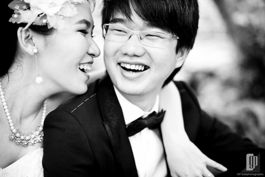 prewedding in ubud bali love happy laugh daylight gorgeous white dress and tuxedo hug from behind