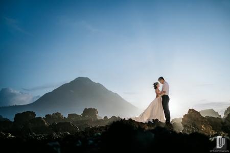 Prewedding in Mountain Batur Bali happy love smile white gown and tuxedo crown sunrise stone larvae mountain