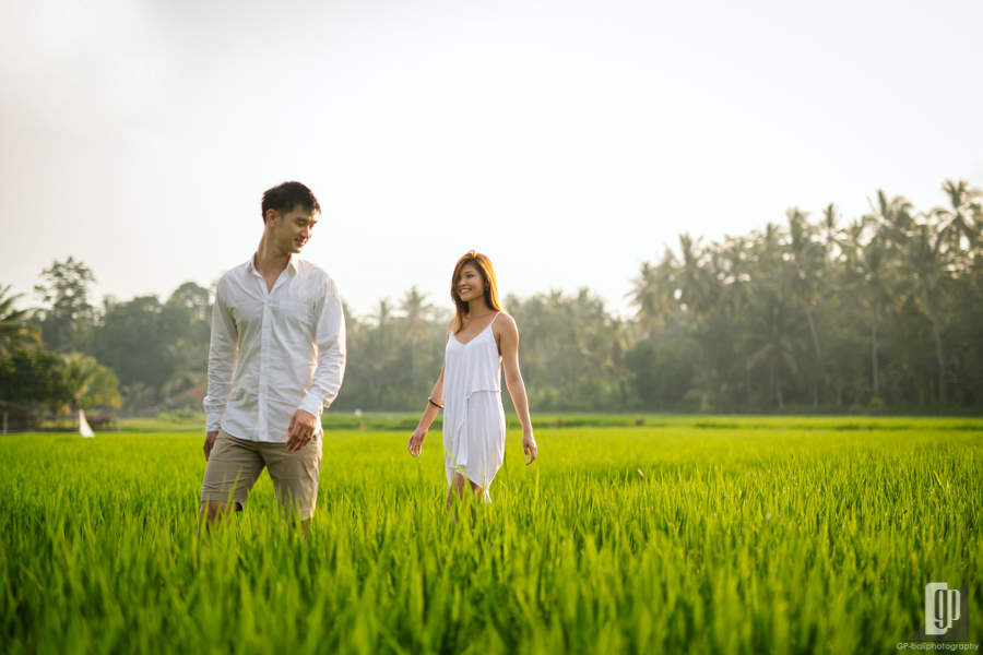Prewedding in Bali happy love smile sunset with orange sky wind with white dress and white shirt casual